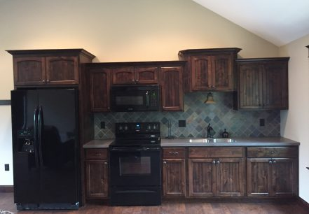dark stained kitchen cabinets and black appliances