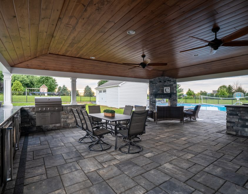 newly built backyard porch with stone flooring and dark wood ceiling