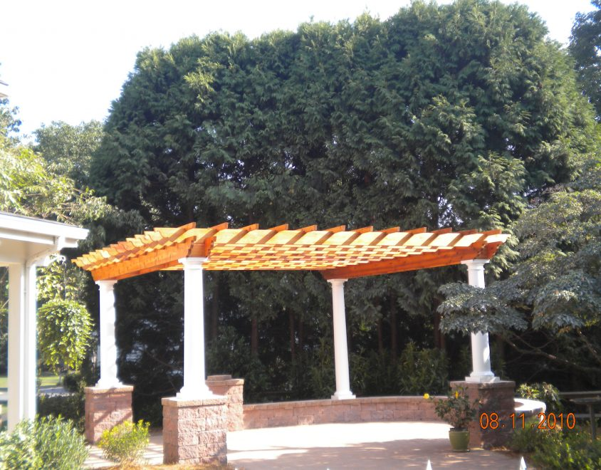 outdoor pergola with white columns and stone support