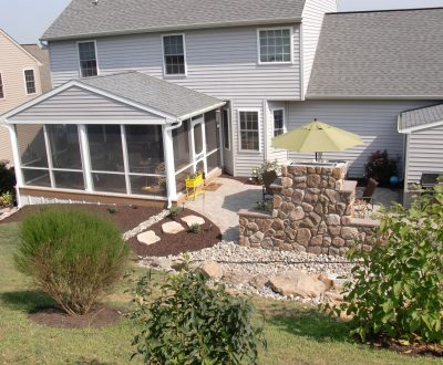 sun room addition on home with outdoor dining area and several bushes