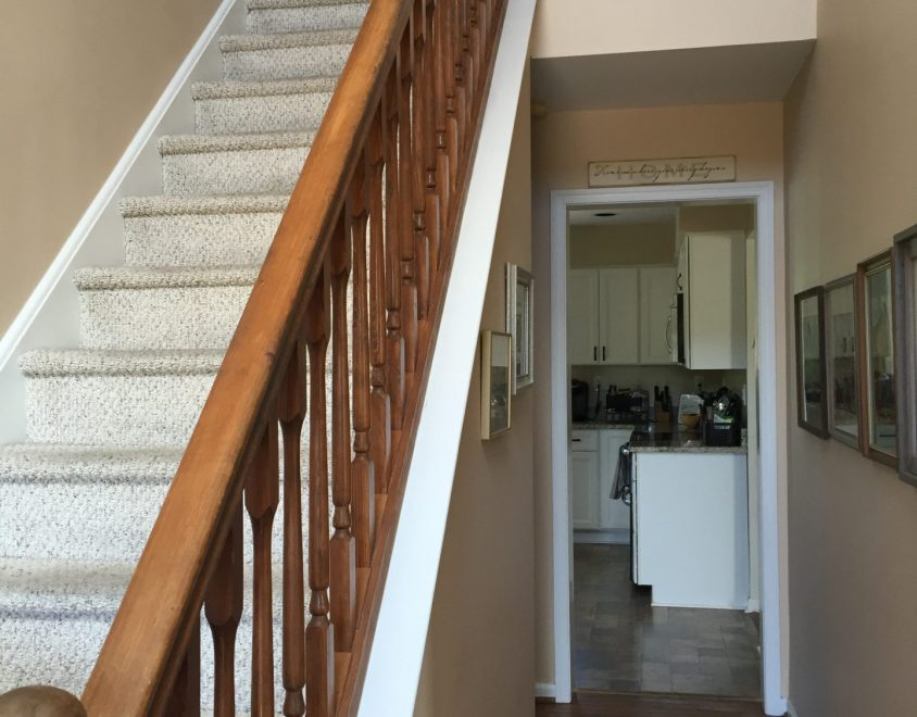 white carpet staircase with wood handrail